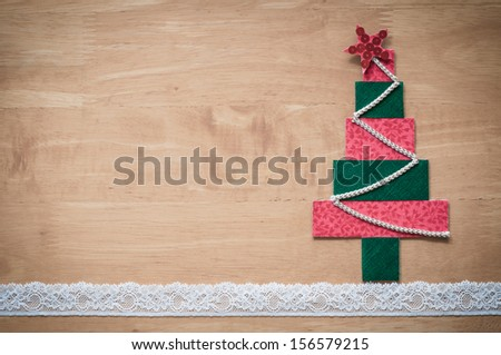 Handmade fabric Christmas tree on wooden background. Copy space for your text. - stock photo