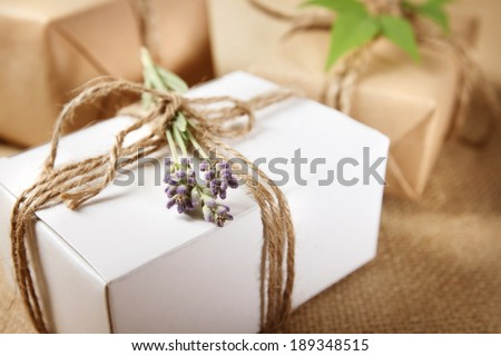 Handmade gift box with lavender sprig on burlap - stock photo
