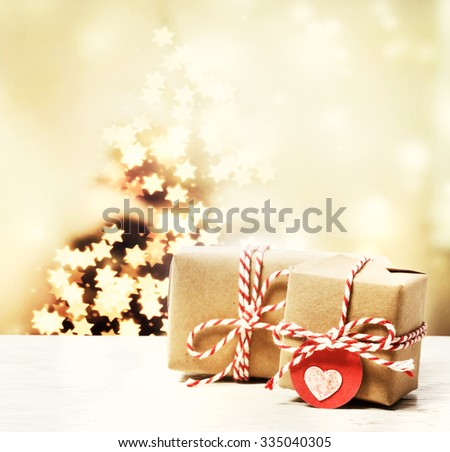 Handmade gift boxes with star shaped lights on Christmas tree - stock photo