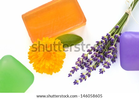 Handmade glycerin soaps with flowers on white background. Natural beauty care - lavender and marigold (Calendula officinalis). - stock photo