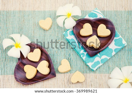 Handmade heart shape cookies on wooden plate and blue napkin Outdoor background Frangipani flower Top view  - stock photo