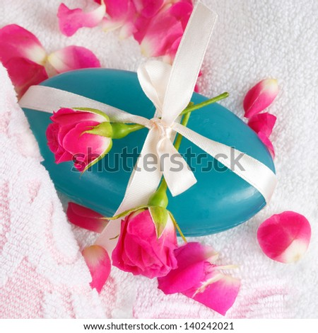 Handmade herbal soap on a towel with flowers - stock photo