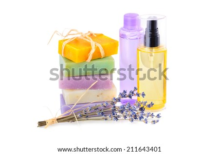 Handmade herbal soaps with lavender flowers and group of lotions in bottles on white background