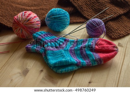 Handmade knitted baby socks and multicolored skeins of thread on light wooden boards