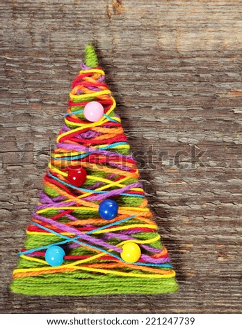 Handmade knitted Christmas tree on old wooden background - stock photo