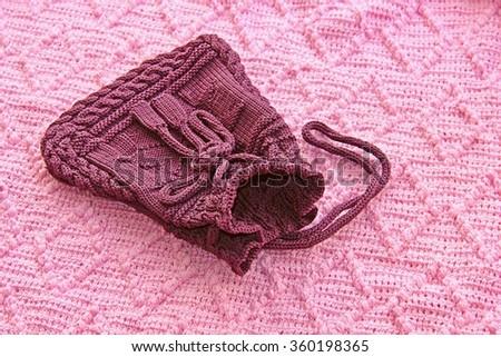 Handmade knitting bag on lozenge pattern knitting background. - stock photo