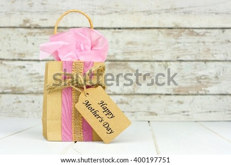 Handmade Mothers Day gift bag with tag against a rustic white wood background - stock photo