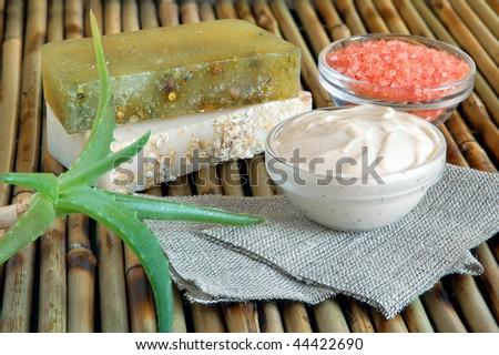 Handmade oatmeal soaps, facial mask, salt and hand cream on green on bamboo mat - stock photo