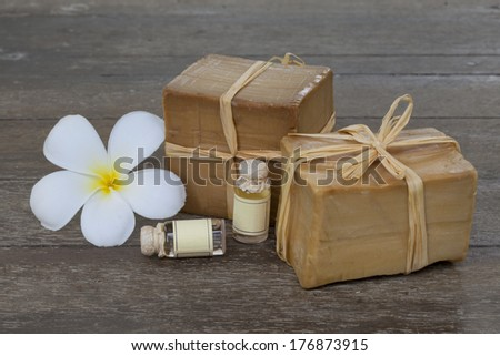 Handmade organic soap with essential oils and frangipani flowers on wooden background - stock photo