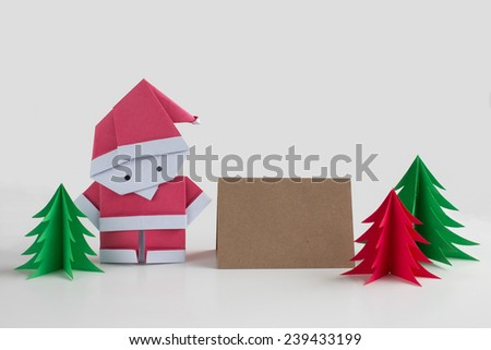 Handmade origami Santa Claus paper craft with christmas trees and a card for writing your own message - stock photo