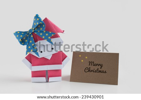 Handmade origami Santa girl paper craft with a card say merry christmas - stock photo