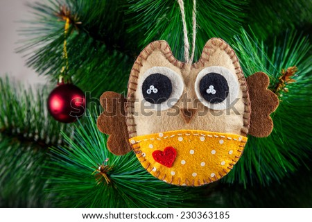 Handmade owl with big eyes from felt on Christmas tree - stock photo
