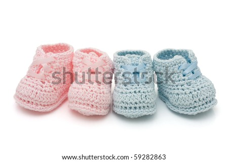 Handmade pink and blue baby booties isolated on a white background