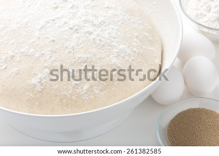 handmade pizza or bread dough in a bowl with fresh eggs, white flour and yeast. close up, horizontal. - stock photo