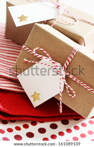 Handmade present boxes with tags on red napkins - stock photo