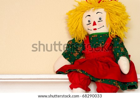 Handmade rag doll in red and green smock - stock photo