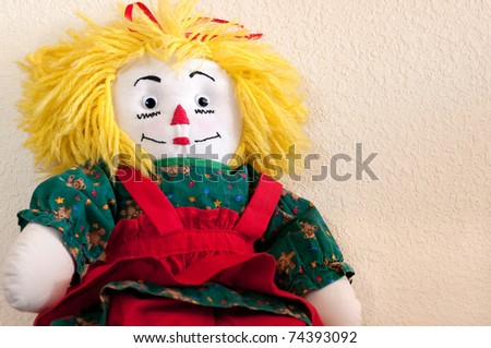 Handmade ragdoll with yellow hair wearing red and green dress against beige background, landscape orientation - stock photo