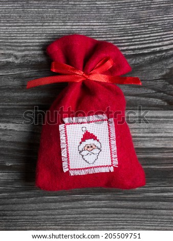 Handmade red christmas sac with a embroidered santa hat on felt. - stock photo