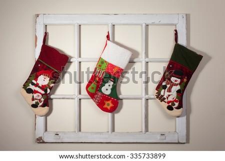 Handmade Santa boots hang on a rustic window frame - stock photo