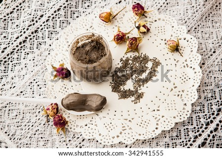 Handmade scrub in clear glass jar on a lace tablecloth - stock photo