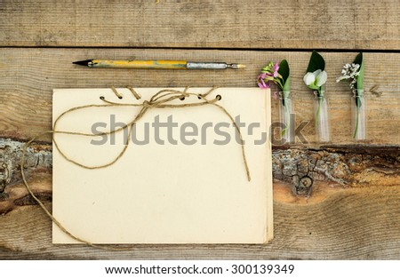 handmade sketchbook with old pen and small bouquet of wildflowers on a wooden background - stock photo