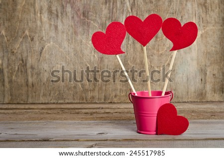 handmade skewers with cloth hearts for celebration of St. Valentine's Day on wooden background - stock photo