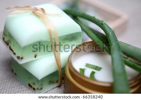 Handmade soap bars, aloe, vera leaves and moisturizer composition. - stock photo