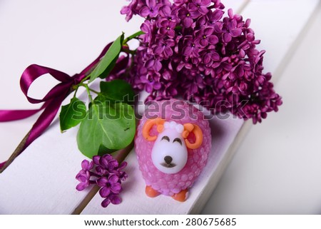 Handmade soap. In the form of a lamb. The branch of lilac with a satin ribbon - stock photo