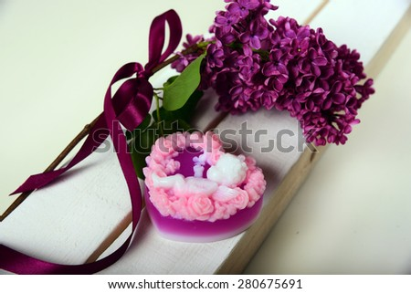 Handmade soap. In the shape of a heart with an angel. The branch of lilac with a satin ribbon - stock photo