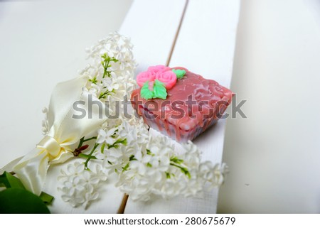 Handmade soap. Shaped Cake. The branch of white lilac with satin ribbon - stock photo