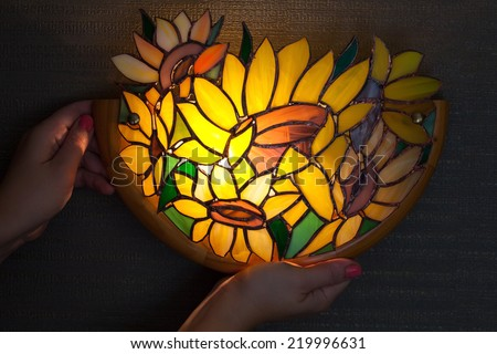 Handmade stained glass lamp with colorful sunflowers in woman's hands - stock photo