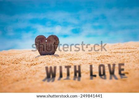 """Handmade stone hard half dug-in in the beach sand by the sea water and """"With Love"""" letters - stock photo"""