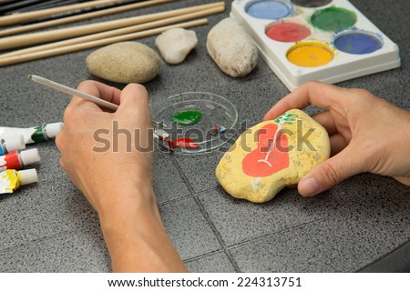 Handmade - stone painting. production decoration. Female hand are drawing red heart on the stone. Horizontally. - stock photo
