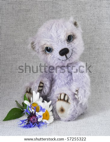 Handmade, the sewed toy: lilac teddy-bear with a bunch of flowers at feet