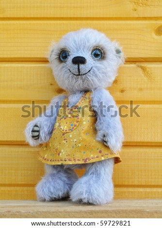Handmade, the sewed toy: teddy-bear Chupa before a wooden wall - stock photo