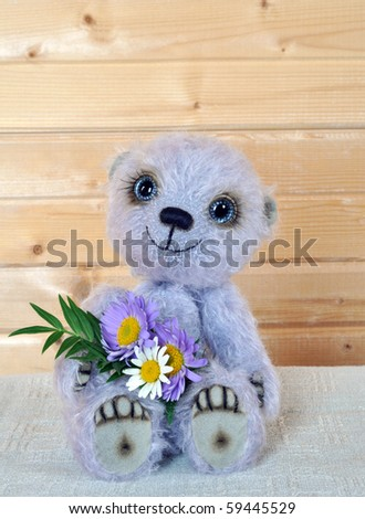 Handmade, the sewed toy: teddy-bear Chupa with a bouquet before a wooden wall