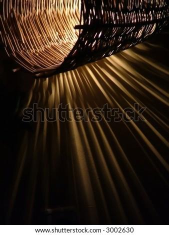 handmade twig lamp on the wall, casting interesting shadows - stock photo