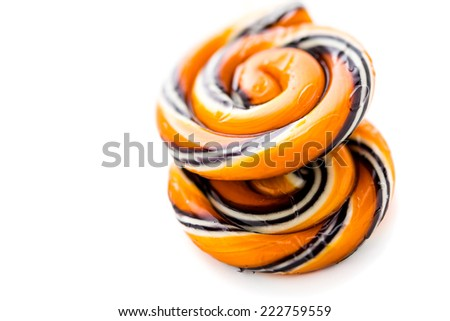 Handmade twist lollipop with orange and black stripes. - stock photo