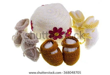 Handmade variety of knitted shoes and booties - stock photo