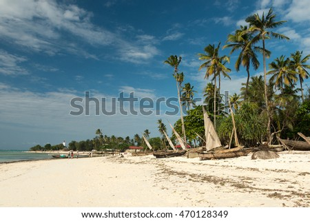 handmade wooden fishing boats on sandy beach of fishing village in Zanzibar
