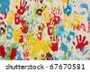 Handprints in different colors in a mural. Background picture. - stock photo