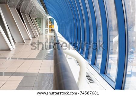Handrail in long corridor of airport - stock photo