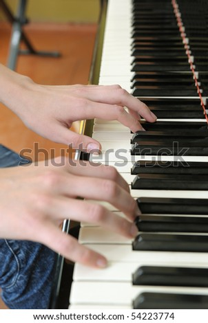 Hands above keys of the piano. A photo close up.