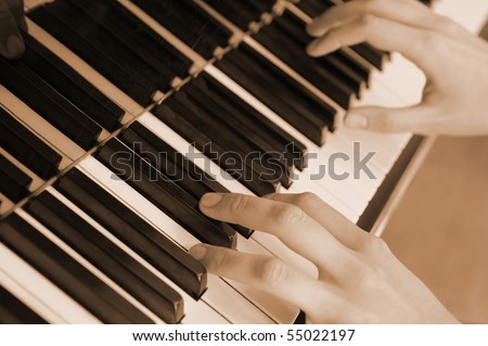 Hands above keys of the piano. A photo close up.Old color