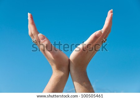 Hands against a blue sky open and cupped
