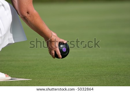 Hands and arm of a female holding a lawn bowling ball about to bowl. - stock photo