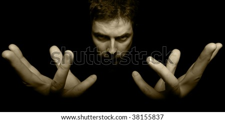 Hands and face of evil magician in darkness - stock photo