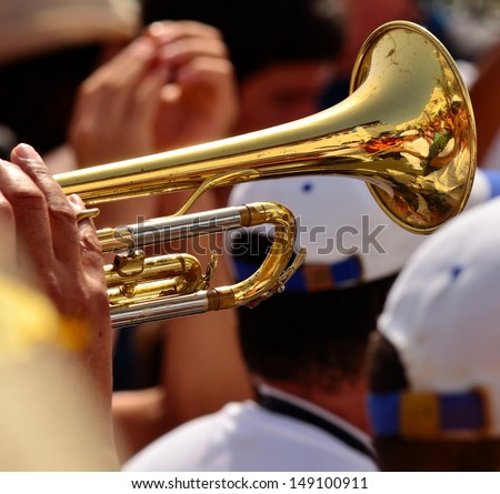 Hands and fingers playing the bright trumpet in a musical band on the street with people applauding and dancing - stock photo