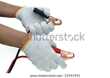 Hands and gloves with car jump start cables - stock photo