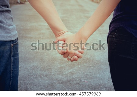 Hands and hearts together. Close-up of loving couple holding hands while walking outdoors. soft focus. vintage tone